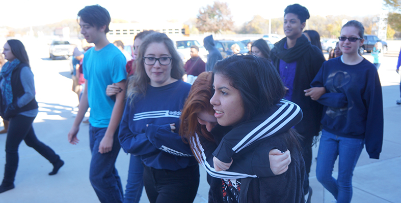 Heritage Students Lean on Each Other During Side by Side Walk